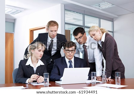 Serious people in business suits looking at laptop monitor