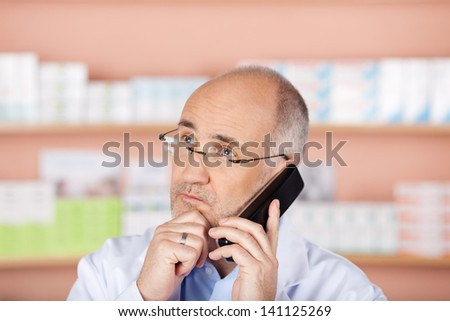 Serious pharmacist listening on the telephone inside the drugstore - stock photo