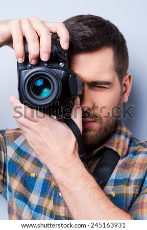 Serious photographer. Portrait of confident young man in shirt holding camera in front of his face while standing against grey background - stock photo