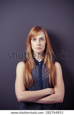 Serious Portrait of a Young Blond Woman with Arms Crossed Over her Stomach, Staring at the Camera on a Gray Background - stock photo
