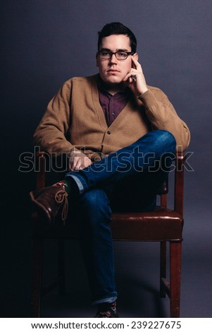 serious portrait of a young man in a sweater vest with fingers on face looking slightly away from camera