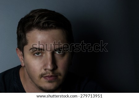 serious portrait of a young man in front of grey background