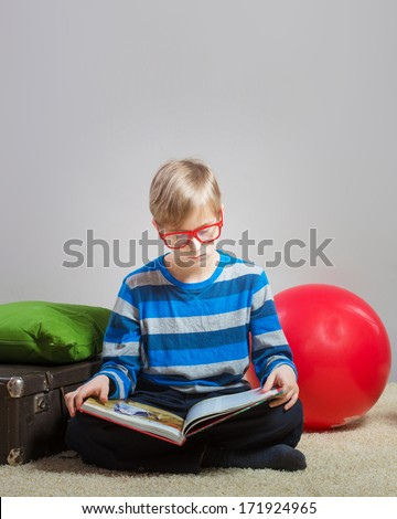 Serious preteen boy sitting on the floor and reading a book, gray background - stock photo