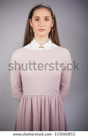 Serious pretty model with pink dress on posing on grey background - stock photo