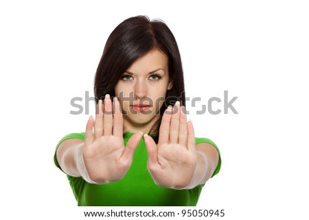 Serious pretty woman making stop hand sign palm gesture, young girl wear green shirt, isolated over white background - stock photo