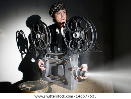 Serious projectionist shows new film - stock photo