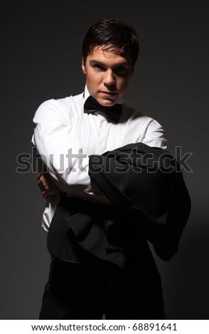 Serious provocative self-confident man wearing white and holding his suit in his hands - stock photo