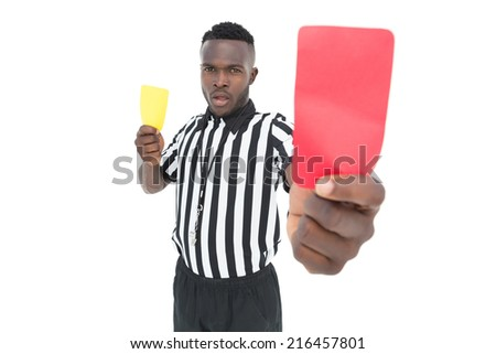 Serious referee showing yellow and red card over white background - stock photo