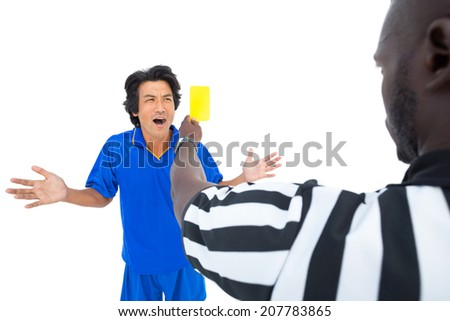 Serious referee showing yellow card to player on white background - stock photo