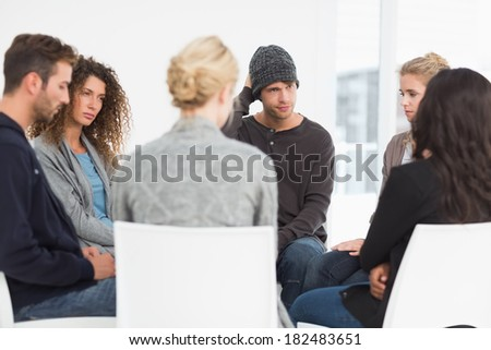 Serious rehab group at therapy session - stock photo