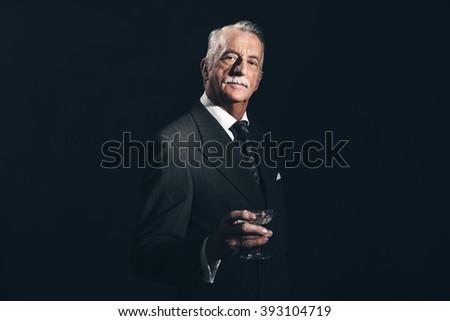 Serious retro 1940s senior businessman holding champagne glass. Studio shot. - stock photo