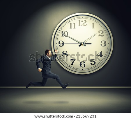 serious running businessman and big white clock in dark room - stock photo