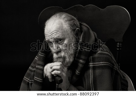 Serious sad old man in his seventies seated with a plaid shawl over his shoulders - stock photo