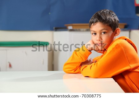 Serious school boy age ten thoughtful in classroom chin on hand