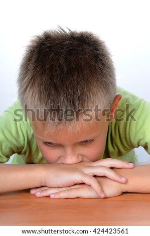 Serious school boy sitting thinking at the table - stock photo