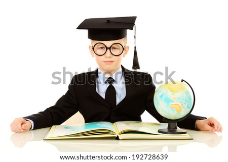 Serious schoolboy in academic hat sitting at the table with a book and globe. Isolated over white. - stock photo