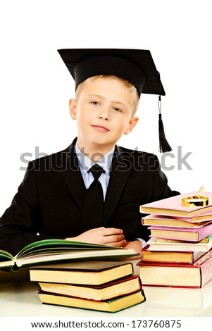 Serious schoolboy in academic hat sitting at the table with books. Isolated over white. - stock photo
