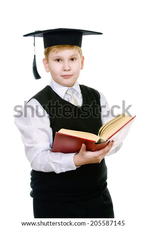 Serious schoolboy in academic hat standing with a book. Isolated over white. - stock photo