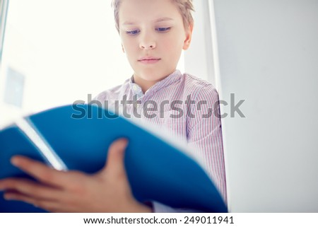 Serious schoolboy reading notes in exercise-book - stock photo