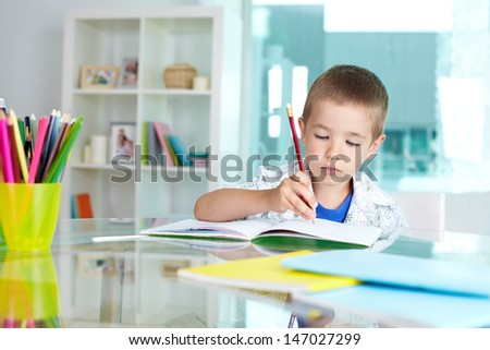 Serious schoolkid drawing with pencil in copybook - stock photo