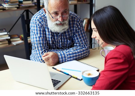 serious senior businessman explaining something to woman and looking at her, smiley young woman listening and looking at laptop in office - stock photo