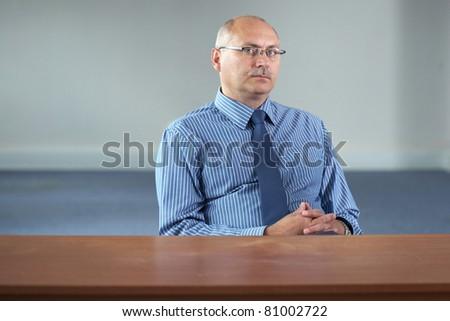 serious senior businessman sits behind empty desk, office shoot - stock photo