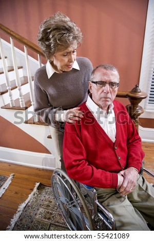 Serious senior couple at home, man in wheelchair