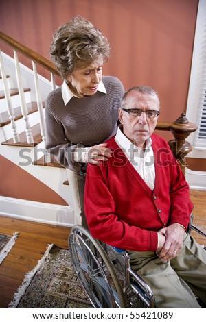 Serious senior couple at home, man in wheelchair - stock photo
