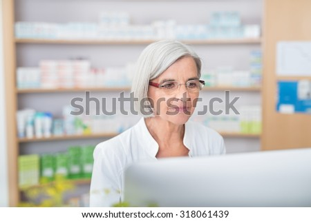Serious senior female pharmacist working on a computer in the pharmacy checking information on the screen - stock photo