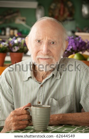 Serious senior man at home with coffee or tea - stock photo
