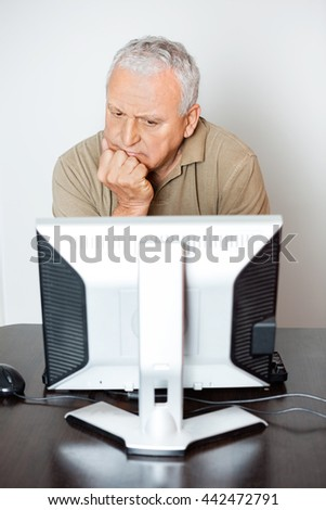 Serious Senior Man Looking At Computer Monitor In Class