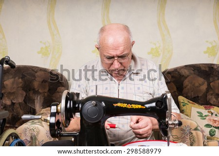 Serious Senior Man Looking Down at Spool of Red Thread and Threading Old Fashioned Manual Sewing Machine at Home in Living Room - stock photo