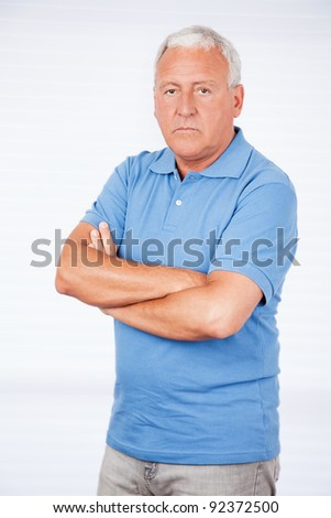 Serious senior man with arms crossed standing against white background