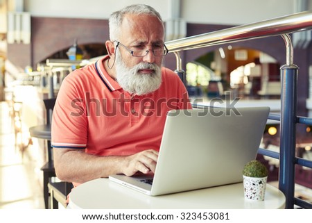 serious senior man working with laptop in cafe - stock photo