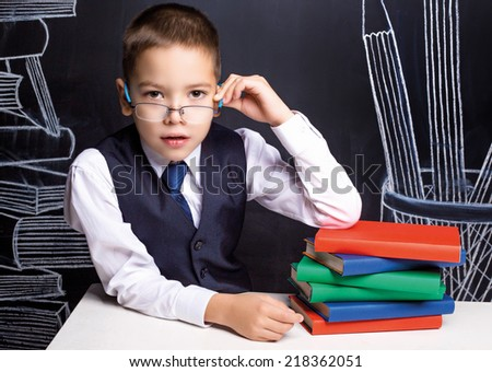 serious seven year old school boy sitting by the table with books - stock photo