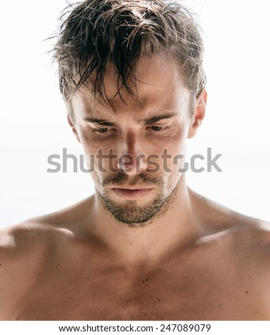 Serious shirtless attractive young man with a goatee staring thoughtfully at the ground, close up head and shoulders isolated on white - stock photo