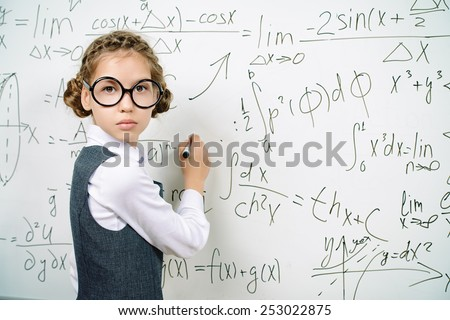 Serious smart schoolgirl in big glasses performs the task at the blackboard. Education. - stock photo