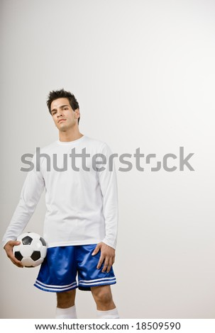 Serious soccer player in uniform holding soccer ball - stock photo