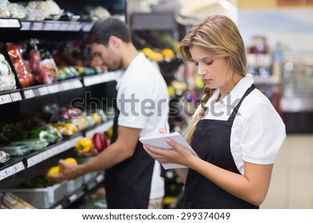 Serious staff woman wrting on notepad at supermarket - stock photo