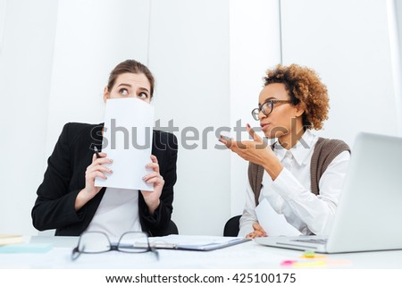 Serious strict african american businesswoman director sitting and talking with her scared young employee in office - stock photo
