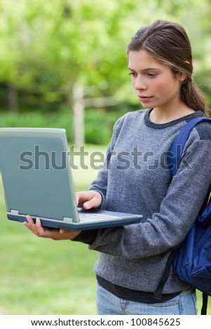 Serious student looking at her laptop while standing upright in the countryside