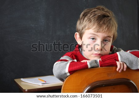 Serious Student resting his head on the back of his chair - stock photo