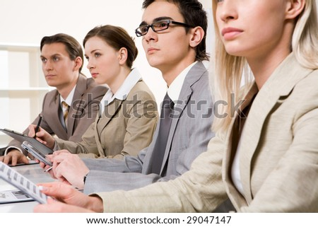 Serious students sitting in row and looking at board during presentation