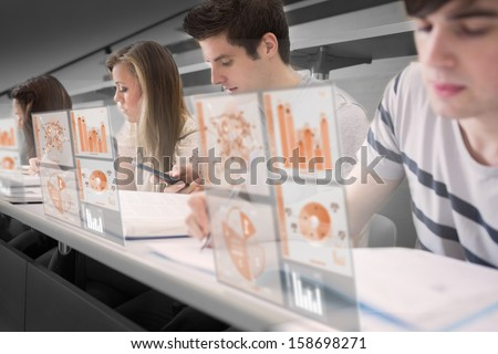 Serious students working on their digital tools in lecture hall - stock photo