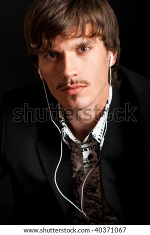 Serious stylish man listening to music against black background - stock photo