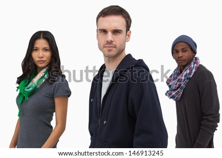 Serious stylish young people in a line on white background - stock photo