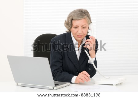 Serious successful senior businesswoman sitting behind office table portrait - stock photo