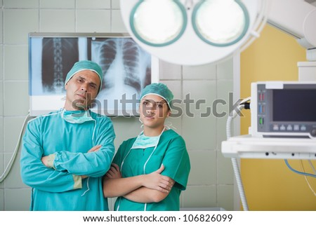 Serious surgeon and a nurse looking at camera in operating theater - stock photo