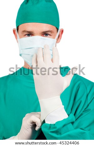 Serious surgeon wearing surgical gloves against a white background - stock photo