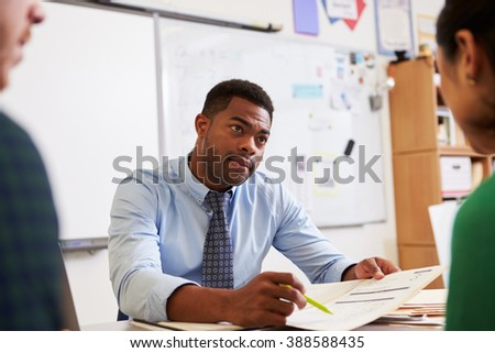 Serious teacher at desk talking to adult education students - stock photo